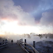 Visitoss walk through the steam emitted from a spectacular geyser at sunset at Te Puia, Rotorua. Te Puia is the premier Maori cultural centre in New Zealand - a place of gushing waters, steaming vents, boiling mud pools and spectacular geysers. Te Puia also hosts National Carving and Weaving Schools and  daily maori culture performances including dancing and singing. Rotorua, 9th December 2010 New Zealand.  Photo Tim Clayton