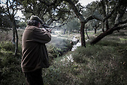 """António Manuel Barata shooting a deer. <br /> <br /> """"The Pose and the Prey""""<br /> <br /> Hunting in my imagination was always more like taxidermy — as if the prey was just a mere accessory of the hunter's pose for his heroic photograph — the real trophy.<br /> <br /> When I decided to document the daily lives of Portuguese hunters, I had in my memory the """"cliché"""" from the photographer José Augusto da Cunha Moraes, captured during a hippopotamus hunt in the River Zaire, Angola, and published in 1882 in the album Africa Occidental. The white hunter posed at the center of the photograph, with his rifle, surrounded by the local tribe.<br /> <br /> It was with this cliché in mind that I went to Alentejo, south of Portugal, in search of the contemporary hunters. For several months I saw deer, wild boar, foxes. I photographed popular hunting and private hunting estates, wealthy and middle class hunters, meat hunters and trophy hunters. I photographed those who live from hunting and those who see it as a hobby for a few weekends during the year. I followed the different times and moments of a hunt, in between the prey and the pose, wine and blood, the crack of gunfire and the murmur of the fields .<br /> <br /> I was lucky, I heard lots of hunting stories. I found an essentially old male population, where young people are a minority. Hunters, a threatened species by aging and loss of economic power caused by the crisis in the South of Europe.<br /> <br /> The result of this project is this series of contemporary images, distant from the """"cliche"""" of 1882.<br /> <br /> — Antonio Pedrosa"""