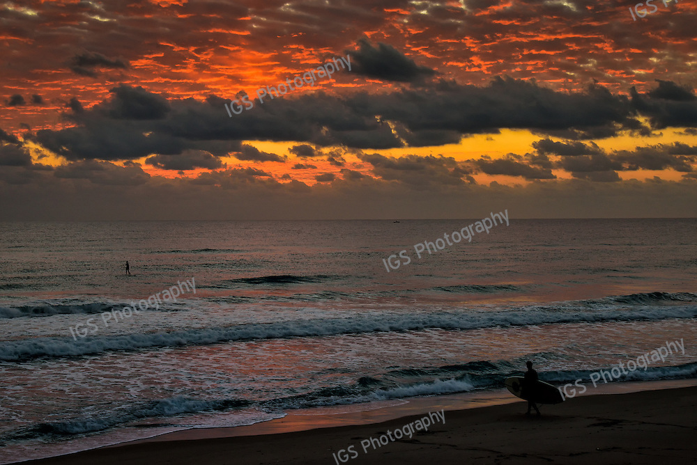 Stand up Paddle surfer heading out  at Sunrise