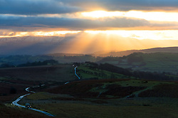 © Licensed to London News Pictures. 03/01/2017. Brecon, Powys, Wales, UK. A four wheel drive vehicle negotiates a small road on The Mynydd Epynt moorland in the foreground as the sunrises over the Brecon Beacons National Park on the horizon. A dusting of snow fell on 1st January on the higher peaks of the Beacons  above approximately 550 metres. The temperature last night in Mid Wales at 100 metres was approximately minus 1 degree centigrade. The moderate wind at 400 metres gave a 'feels like' temperature of about minus 4 degrees centigrade. Photo credit: Graham M. Lawrence/LNP