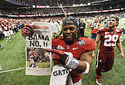 Daily Photo by Gary Cosby Jr.    ..Trent Richardson holds up a newspaper and points to it as he leaves the field after Alabama defeated LSU 21-0 to claim their 14th National Championship...................................