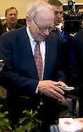 Omaha, Neb 5/6/06 Warren Buffet digs in his wallet to buy ice cream on the floor at the Berkshire Hathaway annual meeting in the Qwest Center Omaha Saturday Morning..(Chris Machian/Prairie Pixel Group)