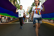 "A color guard with ceremonial rifle stands motionless as two rainbow banners are carried past at LGBT Pride. The annual march through Taipei's city streets is the largest in Asia, with well over 50 000 people taking part. The 2014 event had the theme ""Walk in Queer's Shoes"", to encourage the wider community to lend their support for equal marriage rights."