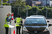 An NHS (National Health Service) worker or care worker is leaving o2 testing Centre after they dropped off testing kit for COVID-19 at a drive-through testing centre in a car park at O2 Testing centre in Greenwich, London, Monday, May 4, 2020. <br /> The UK continues in lockdown to help curb the spread of the coronavirus, which has impacted on nations around the globe imposing self-isolation and exercising social distancing when people move from their homes. (Photo/ Vudi Xhymshiti)