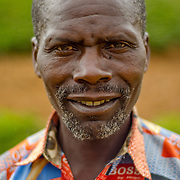 Karera Celestin, a village elder, poses for a portrait near the dried up water source of Burega Pond, Rulindo District, Rwanda.