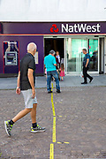 A man steps over the 2 metre social distancing advice line taped to the floor outside NatWest bank on the15th of June 2020 in Folkestone, United Kingdom. The central shopping streets were deserted due to the lock down in place but banks remained open during the lockdown of 2020 as a vital service.
