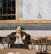 A man sits watching TV, drinking coffee and smoking from a hookah in Al Nawfara Cafe, Damascus, Syria