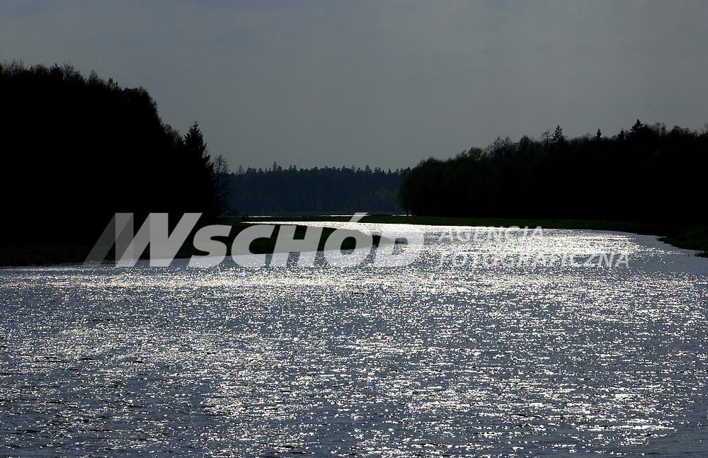 """Kamieniuki, Bialorus, 16.05.2005 r W kwietniu 2005 r zostalo otwarte turystyczne przejscie pomiedzy Polska a Bialorusia w Bialowiezy. Ma ono umozliwic swobodna wymiane turystyczna na obszarze Euroregionu Puszcza Bialowieska. Po stronie bialoruskiej caly obszar puszczy jest Parkiem Narodowym o nazwie """"Bielowiezskaja Puszcza"""". Jednak - ze wzgledow politycznych - jest bardzo duzo utrudnien ograniczajacych mozliwosci zwiedzania. Po pierwsze trzeba miec wize bialoruska, ktora mozna otrzymac w Bialymstoku za oplata 11 USD ( planuje sie otwarcie punktu wydajacego wizy w Hajnowce, ale nie wiadomo kiedy ), po drugie puszcze mozna zwiedzac jedynie z przewodnikiem, za ktorego placi sie 9 USD od osoby. Samodzielne zwiedzanie nie jest mozliwe. Bialorusini najchetniej widza zorganizowane grupy, ktore zawoza do wsi Kamieniuki, do Muzeum Przyrodniczego, autokarem, a puszcze pokazuja z okien busa. Pomimo Parku Narodowego w tej czesci puszczy prowadzona jest intensywna scinka drzew, co rowniez moze byc przyczyna niecheci do turystow z zagranicy *** Kamenyuky. Belovezhskaya Pushcha, also known as the Bialowieza Forest, is located in between the countries of Belarus and Poland *** N/z lesna rzeka Przewloka na ktorej spietrzono zalew o pow. 230 ha fot Michal Kosc / AGENCJA WSCHOD"""