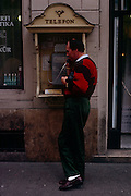 "A Hungarian man stands in an open phone booth to make a call using a landline in a Budapest street. The word Telefon is overhead and this cold-war era technology is in use in 1990. According to Thomas Edison, ""Tivadar Puskas was the first person to suggest the idea of a telephone exchange"". Puskás's idea finally became a reality in 1877 in Boston. It was then that the Hungarian word ""hallom"" ""I hear you"" was used for the first time in a telephone conversation when, on hearing the voice of the person at the other end of the line, Puskás shouted ""hallom"". This cannot be confirmed by any original documents, however it has passed into Hungarian modern folklore. Hallom was shortened to Hello."