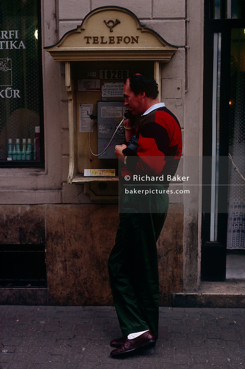 """A Hungarian man stands in an open phone booth to make a call using a landline in a Budapest street. The word Telefon is overhead and this cold-war era technology is in use in 1990. According to Thomas Edison, """"Tivadar Puskas was the first person to suggest the idea of a telephone exchange"""". Puskás's idea finally became a reality in 1877 in Boston. It was then that the Hungarian word """"hallom"""" """"I hear you"""" was used for the first time in a telephone conversation when, on hearing the voice of the person at the other end of the line, Puskás shouted """"hallom"""". This cannot be confirmed by any original documents, however it has passed into Hungarian modern folklore. Hallom was shortened to Hello."""