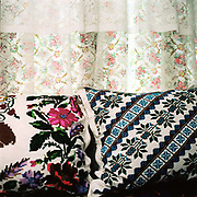 Embroidered cushions and net curtains at the window in the interior of a Romanian peasant farmer's home in the village of Desesti, Maramures, Romania.