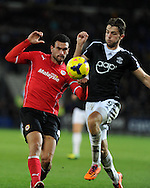 Cardiff city's Steven Caulker and Southampton's Jay Rodriguez ®. .Barclays Premier league, Cardiff city v Southampton at the Cardiff city Stadium in Cardiff,  South Wales on Boxing day, Thursday 26th Dec 2013. <br /> pic by Andrew Orchard, Andrew Orchard sports photography.