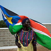 A South Sudanese woman poses with the national flag during a mock parade in preparation for independence day in central Juba.