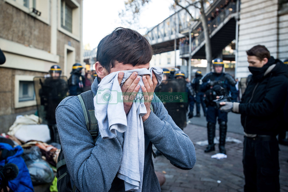 October 31, 2016 - Paris, France - Migrants cprotecting his eyes after some teargas was thrown by the police in Paris, France on 31 October 2016. More migrants and refugees coming from the dismantling of Calais and also from Italy are living in the streets of Paris, between the Stalingrad and Jaures tube Stations, in the north of the French capital. The police evacuates one of the camp, with migrants from Afgahnistan and Pakistan. (Credit Image: © Guillaume Pinon/NurPhoto via ZUMA Press)