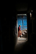 A Kinnauri woman walks up the stairs in her home in the village of Nesang, Himachal Pradesh, India