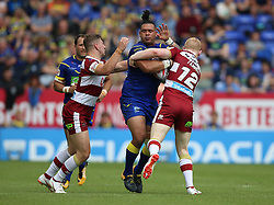Warrington Wolves Ben Murdoch-Masila is tackled by Wigan Warriors George Williams (left) and Liam Farrell (right) during the Ladbrokes Challenge Cup, quarter final match at the Halliwell Jones Stadium, Warrington.