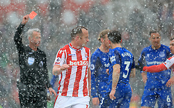 Stoke City's Charlie Adam is shown the red card by referee Martin Atkinson during the Premier League match at the bet365 Stadium, Stoke.