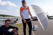 Wil Baselmans wordt met een paraplu uit de zon gehouden. In Lausitz bereidt het Human Power Team Delft en Amsterdam zich met fietser Wil Baselmans voor op het uurrecord met de VeloX3. In september wil het team, dat bestaat uit studenten van de TU Delft en de VU Amsterdam, een poging doen het wereldrecord snelfietsen te verbreken, dat nu op 133 km/h staat tijdens de World Human Powered Speed Challenge.<br /> <br /> At the Dekra test track in Lausitz the Human Power Team Delft and Amsterdam is preparing the VeloX3 with rider Wil Baselmans for the attempt to set a new world hour record on a bicycle. With the special recumbent bike the team, consisting of students of the TU Delft and the VU Amsterdam, also wants to set a new world record cycling in September at the World Human Powered Speed Challenge. The current speed record is 133 km/h.