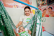 Oct. 6, 2009 -- SAMUT SAKHON, THAILAND: KHAI plays with her 8 month old daughter KHANWAND in their one room tenement in Samut Sakhon, Thailand. Khai came to Thailand from a village near Myawaddy, Burma to work in a fish processing plant in Samut Sakhon. The Thai fishing industry is heavily reliant on Burmese and Cambodian migrants. Burmese migrants crew many of the fishing boats that sail out of Samut Sakhon and staff many of the fish processing plants in Samut Sakhon, about 45 miles south of Bangkok. Migrants pay as much $700 (US) each to be smuggled from the Burmese border to Samut Sakhon for jobs that pay less than $5.00 (US) per day.   Photo by Jack Kurtz / ZUMA Press