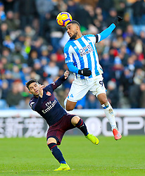 Arsenal's Lucas Torreira (left) and Huddersfield Town's Elias Kachunga battle for the ball during the Premier League match at the John Smith's Stadium, Huddersfield.