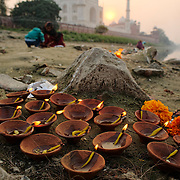 Families preparing offering in the Yamuna river behind the Taj Mahal