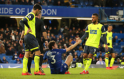Chelsea's Marcos Alonso (centre) is helped off the ground by Huddersfield Town's Elias Kachunga (right)