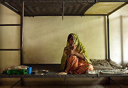 Azra, 30, who was burned with acid by her brother-in-law, is seen eating lunch by herself in her room, Lahore, Pakistan, May 2, 2003. She refuses to eat with the other residents because she is embarrassed of her looks and now cries every time she has to show her face. Azra now lives at Dastak, a shelter opened in 1990 for abused women seeking refuge by the AGHA Legal Aid Cell. Authorities at the shelter say they have arranged medical care and treatment for her burns and scarring.