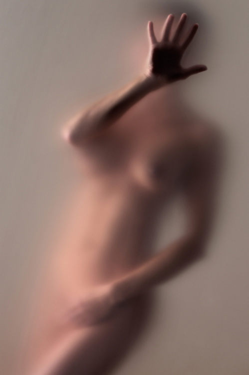 Side lit nude woman behind diffusion screen