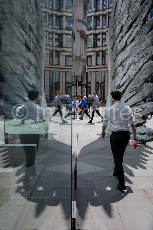 Financial industry businessmen walk past the sculpture entitled City Wing on Threadneedle Street in the City of London, the capitals financial district aka the Square Mile, on 11th July 2019, in London, England. City Wing is by the artist Christopher Le Brun. The ten-metre-tall bronze sculpture is by President of the Royal Academy of Arts, Christopher Le Brun, commissioned by Hammerson in 2009. It is called 'The City Wing' and has been cast by Morris Singer Art Founders, reputedly the oldest fine art foundry in the world.