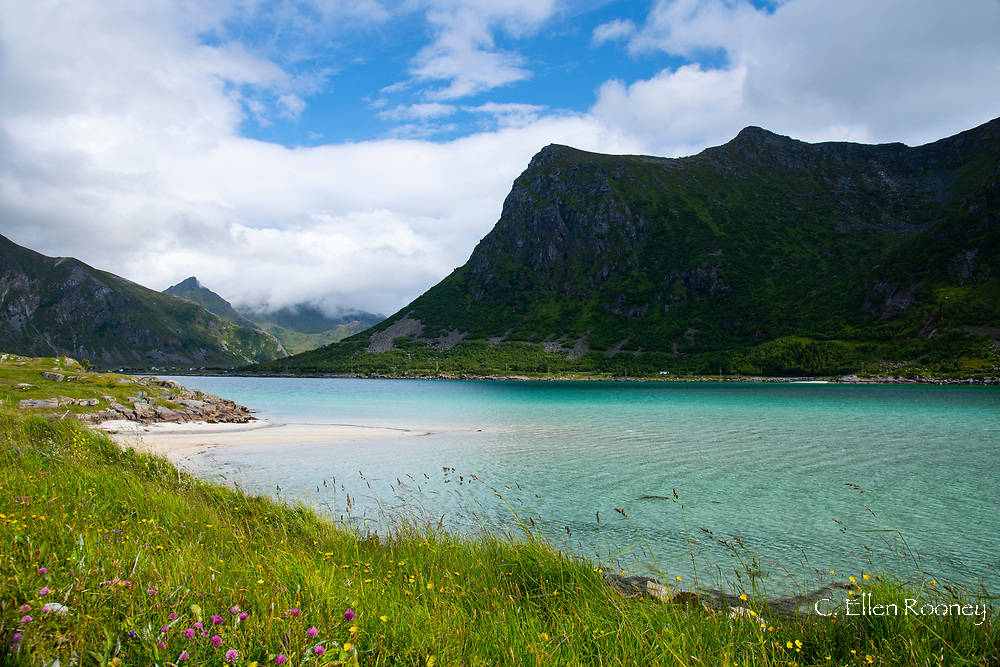 Aqua coloured water in Flakstadpollen, a sea bay surrounded by mountains, Flakstadoy, Lofoten Islands, Norway