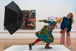 "© Licensed to London News Pictures. 28/09/2020. LONDON, UK. A staff member poses with ""Air Kid (Girl)"" by Yinka Shonibare RA.  Preview of the Summer Exhibition at the Royal Academy of Arts in Piccadilly which, due to the Covid-19 lockdown, is taking place for the first time in the autumn.  Over 1000 works in a range of media by Royal Academicians, established and emerging artists, feature in the exhibition which runs from 6 October 2020 – 3 January 2021.  Photo credit: Stephen Chung/LNP"