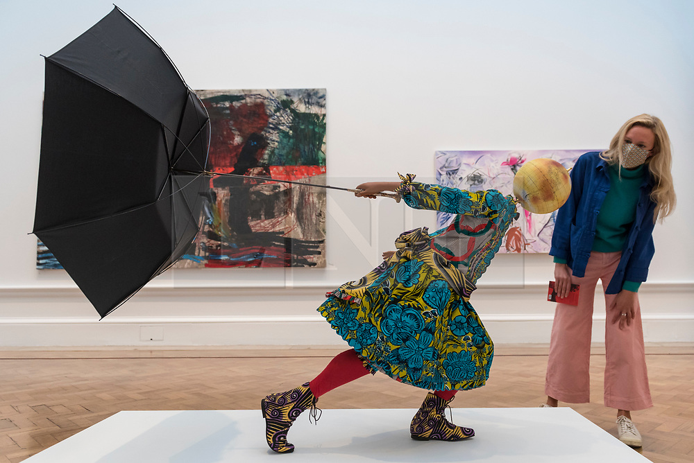 """© Licensed to London News Pictures. 28/09/2020. LONDON, UK. A staff member poses with """"Air Kid (Girl)"""" by Yinka Shonibare RA.  Preview of the Summer Exhibition at the Royal Academy of Arts in Piccadilly which, due to the Covid-19 lockdown, is taking place for the first time in the autumn.  Over 1000 works in a range of media by Royal Academicians, established and emerging artists, feature in the exhibition which runs from 6 October 2020 – 3 January 2021.  Photo credit: Stephen Chung/LNP"""
