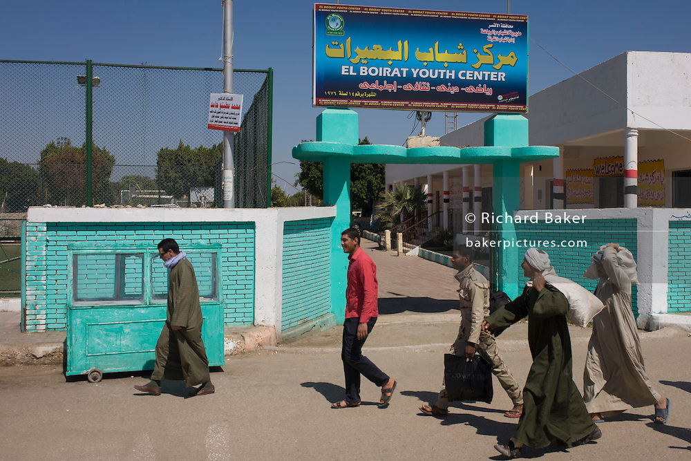 Commuters walk past a youth centre in the village of Bairat on the West Bank of Luxor, Nile Valley, Egypt.