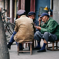Chinese men play cards on a sidewalk in Chengdu.