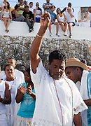 Male Babalowo preist of Candomble group in traditional white dress taking part in a public ceremony on the beach. February 2nd is the feast of Yemanja, a Candomble Umbanda religious celebration, where thousands of adherants visit the Rio Vermehlo Red River to make offerings of flowers and prayers, paying their respects to Yemanja, the Orixa goddess of the Sea and water.