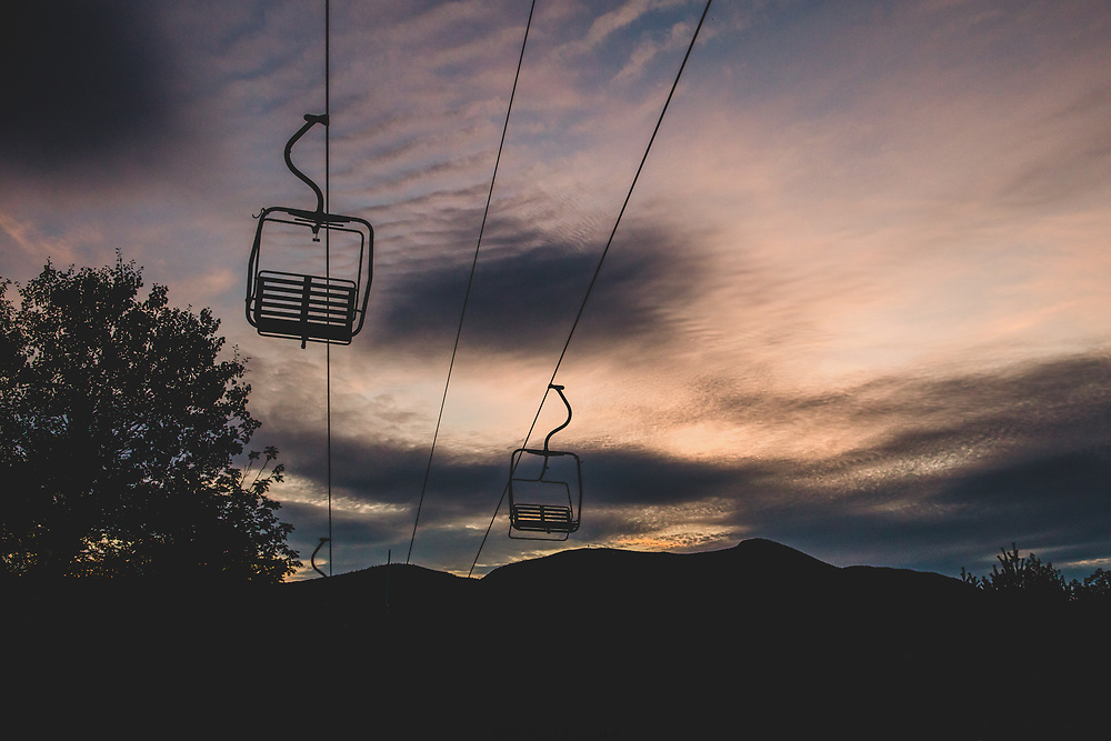 Chairlift seats sitting idle against a stunning summer sunset in Waterville Valley.