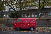 Small van, a Bedford Rascal, playfully covered in flowers painted on it's exterior. London, UK. This tiny vehicle is a little mobile workshop for it's owner. A small business on colourful wheels.