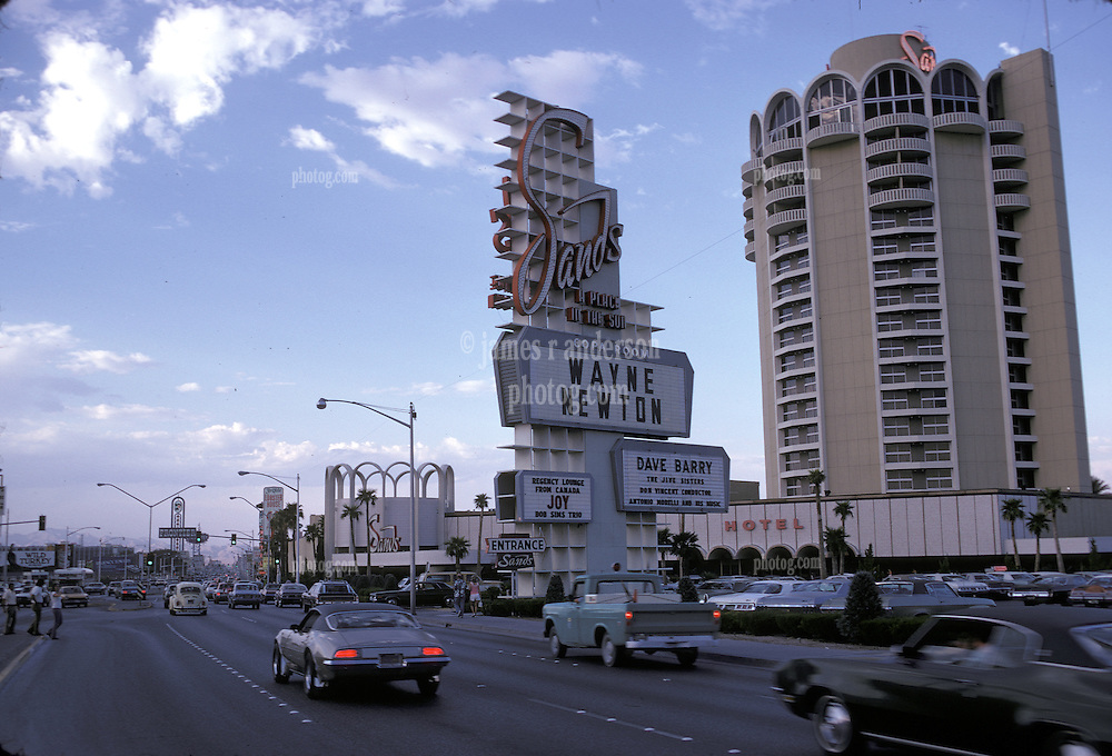 The Las Vegas Strip as it appeared on July 28, 1973. Photo features The Sands Hotel & Casino with Wayne Newton on marquee late in setting sun light.