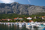 The pleasure boat harbour and the village and mountain. Mount Sveti Ilija mountain. Orebic town, holiday resort on the south coast of the Peljesac peninsula. Orebic town. Peljesac peninsula. Dalmatian Coast, Croatia, Europe.