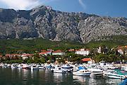 The pleasure boat harbour and the village and mountain. Mount Sveti Ilija mountain. Orebic town, holiday resort on the south coast of the Peljesac peninsula. Orebic town. Peljesac peninsula. Dalmatian Coast, Croatia, Europe.