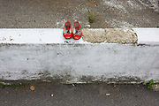 A pair of womens' red shoes have been left on a white wall in south London. With rough plaster on the top of the wall and weeds growing at the foot of the dividing section of cement, the red shows look like Judy Garland's Dorothy's shoes in the Wizard of Oz movie. There is also a tradition of film titles, music and a fairy tale by Hand Christian Anderson that are inspired by Red Shoes as a cultural theme.