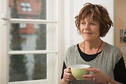 Senior woman having a cup of tea and thinking at home, Munich, Bavaria, Germany