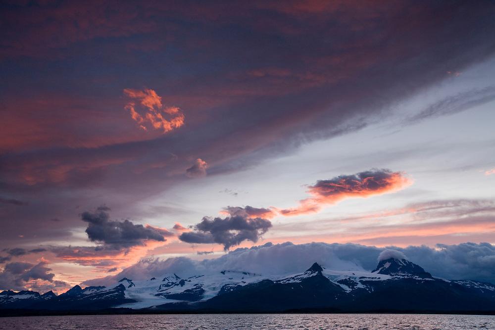 USA, Alaska, Katmai National Park, Midnight sun lights clouds above mountains along Hallo Bay at sunset on summer evening