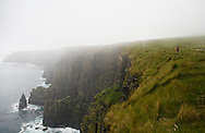 Hiker walking along the Cliffs of Moher, County Clare, Ireland