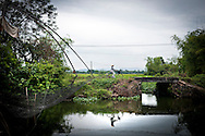 A vietnamese woman crosses a calm river on her bicycle, Hue's countryside, Vietnam, Southeast Asia