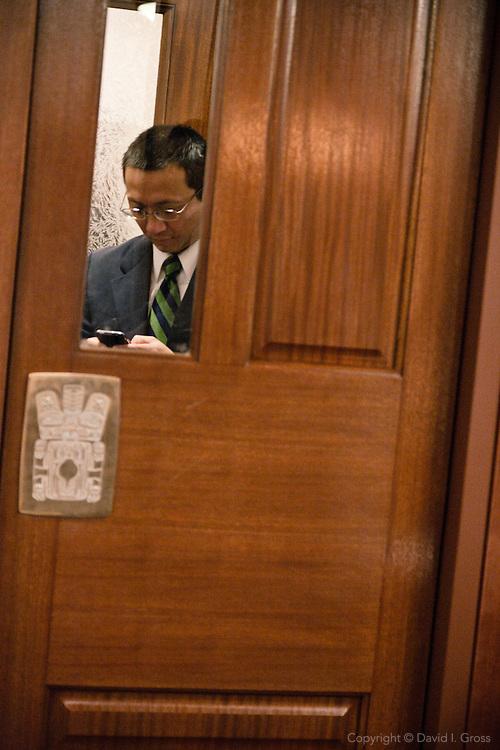 Rep. Scott Kawasaki (D)texts in the entrance to the Alaska State House of Representatives.