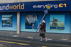 "© Licensed to London News Pictures . 10/12/2014 . Blackpool , UK . A woman wearing a Santa hat stands in to wind and grips a street sign for support on Adelaide Street West . An explosive cyclogenesis - a fast developing storm in which air pressure falls rapidly - known as a "" weather bomb "" - hits the North of England , bringing storms to the region . Photo credit : Joel Goodman/LNP"