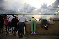 People looking over the wall into the water along the outskirts of Old San Juan, Puerto Rico