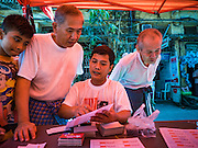 31 OCTOBER 2015 - YANGON, MYANMAR:A National League for Democracy outreach workers explain voting procedures to people in Yangon. Political parties are in full campaign mode in Myanmar (Burma). National elections are scheduled for Sunday Nov. 8. The two principal parties are the National League for Democracy (NLD), the party of democracy icon and Nobel Peace Prize winner Aung San Suu Kyi, and the ruling Union Solidarity and Development Party (USDP), led by incumbent President Thein Sein. There are more than 30 parties campaigning for national and local offices.      PHOTO BY JACK KURTZ