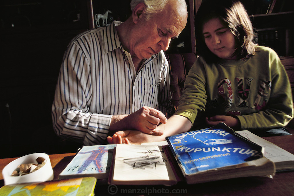 In his Sarajevo apartment, Lokman Demirovic demonstrates acupuncture technique on his granddaughter Nadja, in Bosnia and Herzegovina. From coverage of revisit to Material World Project family in Sarajevo, Bosnia & Herzegovina, 2001.  ©2005 Hungry Planet: What the World Eats